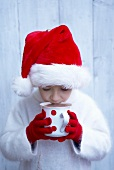 Boy in Father Christmas hat drinking mug of hot chocolate