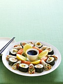Assorted sushi and rice paper rolls on plate