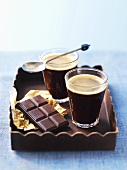Two glasses of coffee and chocolate on tray