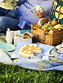 Picnic with fruit in picnic basket and mango cheesecake