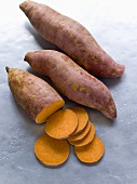 Three sweet potatoes, one partly sliced