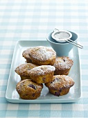 Plum muffins sprinkled with icing sugar