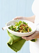 Woman holding dish of bean & chick-pea salad with coriander