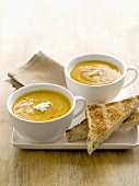 Two cups of carrot and lentil soup with toast triangles