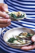 Someone holding a dish of oysters with spinach and cream