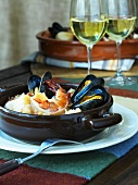 Seafood stew and two glasses of white wine