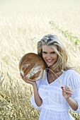 Blond woman with loaf of bread in a cornfield