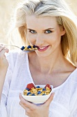 Blond woman with cornflakes and berries out of doors