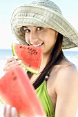 Young woman eating watermelon on beach
