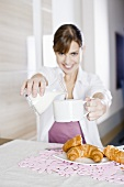 Young woman pouring milk into coffee at table, croissants