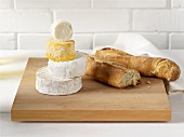 A selection of soft cheeses and baguette on chopping board