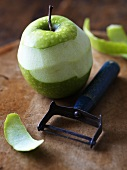 Half-peeled green apple with peeler on wooden background