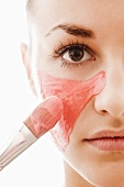 Woman applying red facial mask with brush