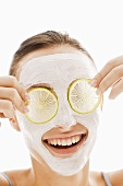 Woman with facial mask and slices of lime over her eyes
