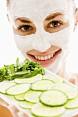 Woman with facial mask holding tray of vegetables & herbs