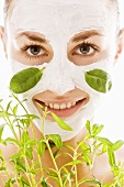 Young woman with herbal facial mask and fresh herbs