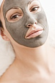 Woman with healing clay facial mask