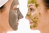 Two women with herbal and with healing clay face masks