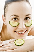 Young woman with cucumber slices under her eyes & on her hand