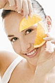 Young woman holding orange slices in front of her face