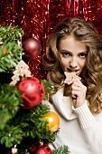 Young woman with biscuit by Christmas tree