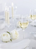 Glass of white wine on table laid for special occasion
