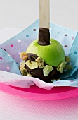 Chocolate-coated green apple with dried fruit for children