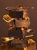 Stack of pieces of chocolate, nuts and baking utensils