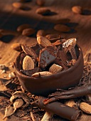 Chocolate bowl with pieces of chocolate and almonds