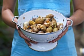 Woman holding sea snails in a colander