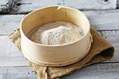 Wholemeal flour in a sieve on jute sack