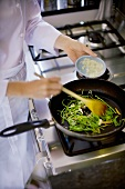 Female chef sautéing green beans with onions