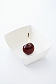 A cherry in a paper dish
