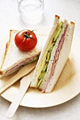 Ham, cheese and cucumber club sandwiches with tomato