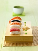 Five nigiri sushi with wasabi and ginger