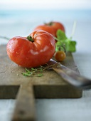 Washed beefsteak tomatoes on a chopping board