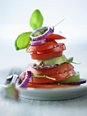 Tower of tomato slices, onion rings and basil