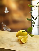 Lemon and lemon wedges with leaves on wooden table