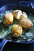 Hasselbackspotatis in a frying pan with butter