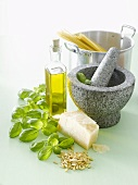 Ingredients for pesto, mortar and pestle, spaghetti in pan