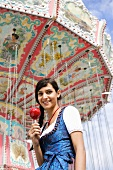 Woman in dirndl with toffee apple in front of swing ride (Oktoberfest)