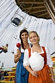 Two women with toffee apple & candy floss by swing ride(Oktoberfest)