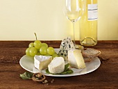 Cheese plate with grapes and bread, white wine