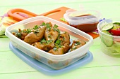 Chicken legs with parsley in a plastic box