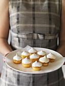 Girl holding a plate of lemon meringue tartlets