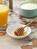 Honey dipper in a dish, yoghurt, orange juice