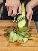 Man making cucumber ribbons with a vegetable peeler