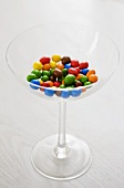Different coloured chocolate-coated peanuts in a glass