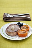 Bacon-wrapped tournedos with grilled tomatoes and olives