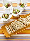 Smoked salmon sandwiches and salad in boxes